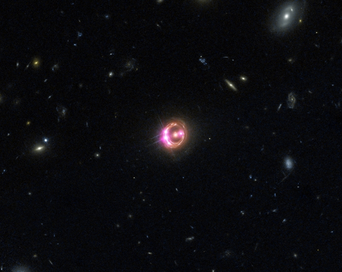 This composite image generated from the Chandra (pink) and Hubble (red, green, blue) telescopes shows the quasar RX J1131, which surrounds a black hole about six billion light years away from Earth. Image credit: Image Credit: NASA/CXC/Univ of Michigan/R.C.Reis et al; Optical: NASA/STSc